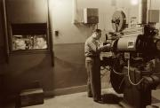 Man working with projector in movie theater 1958